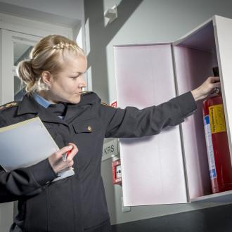 Palotarkastaja tarkastaa käsisammutinta
