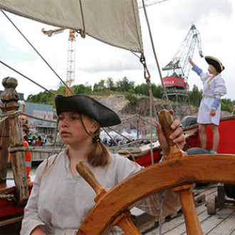 Merimieshattuun pukeutunut tyttö laivan ruorissa.