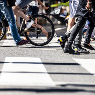 Suojatie ja sitä ylittäviä ihmisiä. Kuva on rajattu ihmisten jalkoihin.