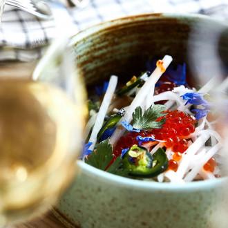 Kaunis ruokakuva, jossa viinilasi ja annos keraamisessa kipossa