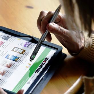 Seniori selailee e-kirjoja tabletilla