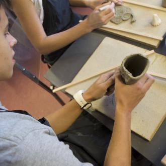 Tummatukkainen nuori mies muotoilee savesta keramiikka-astiaa.