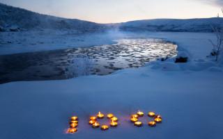 Kynttilöistä muodostuva luku 100 lumihangessa