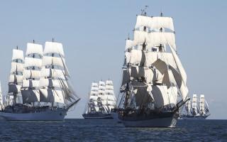 Viisi purjelaivaa avoimin purjein merellä.