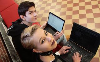 ICT-lukiolaiset Miska Kytö ja Jasmin Heino kannettavien tietokoneiden kanssa istumassa penkillä.