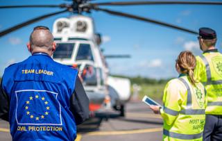 Pelastuslaitoksen Host Nation Support -hankkeen asiantuntijoita Rajavartiolaitoksen helikopterin edessä.
