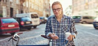 Mies nojaa kadulla polkupyöräänsä ja selaa puhelintaan kahvimuki kädessä