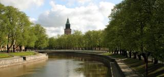 Kuvan taustalla pilkottaa Tuomiokirkon torni ja kuvan keskellä virtaa puiden reunustama Aurajoki.
