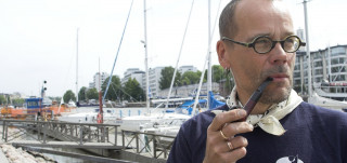 Mies polttaa piippua, taustalla aurajoen venesatama ja föri