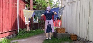 Kylämäen emäntä ripustamassa pyykkiä narulle