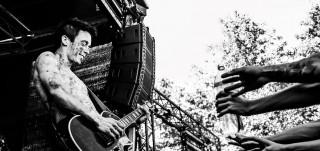 Fanit kurottavat kohti festari-lavalla soittavaa kitaristia