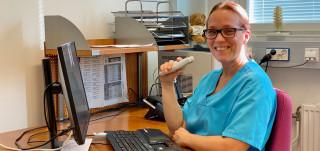 Naislääkäri istuu työpöydän ääressä sanelin kädessään.