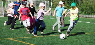 Lapset pelaavat jalkapalloa nurmella