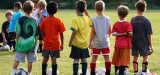 Pienet jalkapalloilijat rivissä nurmella