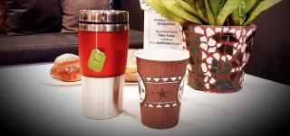 Kertakäyttöinen kahvikuppi ja punainen termosmuki pöydällä.