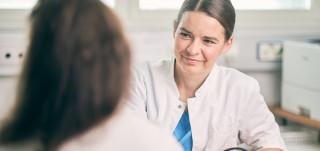 Naislääkäri kuuntelee potilasta vastaanottohuoneessa.