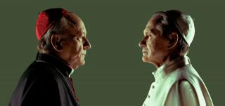 Kaksi ikämiestä puolikuvassa vastakkain, toisella kardinaalin, toisella paavin asu.