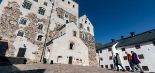 Neljä ihmistä seisoo Turun linnan sisäpihalla.