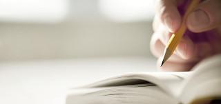 Käsi kirjoittamassa lyijykynällä kirjaan