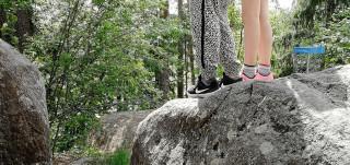 Kaksi lasta seisoo ison kiven päällä.