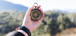 Miehen kädessä on kompassi