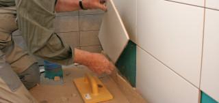 remonttimies laatoittaa wc:n seinää valkoisilla isoilla laatoilla