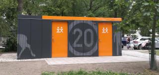 Kupittaanpuiston uusi yleisö-wc, harmaat liikennepuistoaihein kuvioidut seinät kirkkaan oransseilla ovilla ja kattolipalla