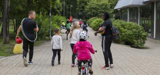 Kaksi liikuntaohjaajaa ja lapsia kävellen ja pyörällä.