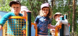 Kolme tyttöä ja kaksi poikaa lippikset päässä leikkipuistossa