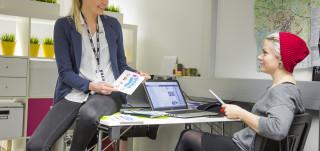 Naiset keskustelevat toimistossa