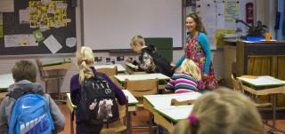 Luokkahuone, jossa oppilaita ja opettaja