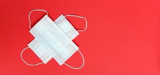 kahdet maskit ristikkäin punaisella pohjalla