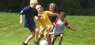 Joukko lapsia pelaa jalkapalloa