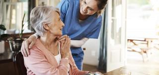 Iäkäs nainen istuu pyörätuolissa ja hoitaja kumartuu katsomaan häntä silmiin.