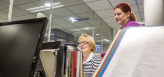 Kaksi naista tietokoneen äärellä.