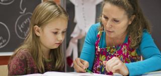 Opettaja auttaa oppilasta