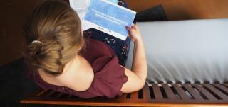 Nainen lukee sohvalla liityntäpysäkointisuunnitelmaa