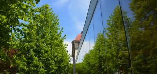 Pääkirjaston uuden puolen lasiseinä ja vanhan puolen torni.