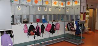 Koulun käytävällä reppuja naulakossa