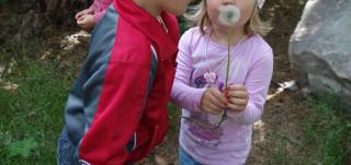 Tyttö ja poika puhaltavat voikukkaa