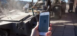 Ihminen puhelin kädessä puhdistusauton vieressä