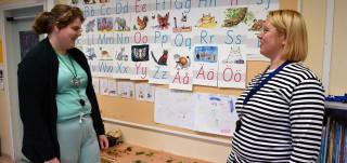 Kaksi naista juttelevat koululuokassa