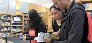 Yksi ihminen lainaa kirjaa kirjastossa, kaksi ihmistä lukevat kirjaa.