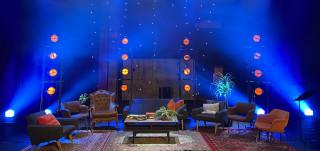 Olohuonemainen lavastus siniseksi valaistulla näyttämöllä