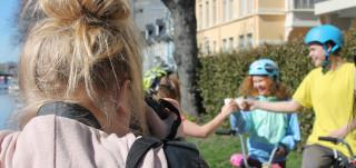Henkilö kuvaa takaapäin ihmisiä, jotka kilistävät muovimukeilla polkupyörien selässä.