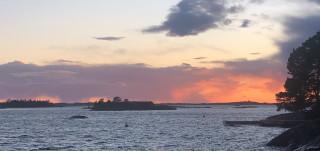 Värikäs iltarusko saaristossa meren ja saarten horisontissa.