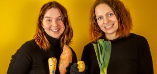 kaksi naista hymyilevät, käsissään vihanneksia, keltainen tausta