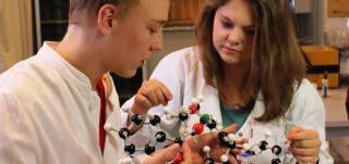 Kaksi oppilasta ja molekyylipienoismalli
