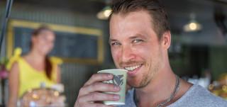 Mies juo kahvia ja hymyilee