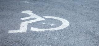 Vammaispysäköintipaikka merkattu asfalttiin pyörätuolisymbolilla